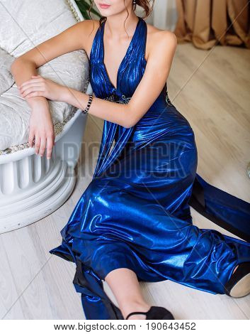 Young Beautiful Slim Brunette Girl In Long Blue Dress With Open Shoulders And Decollete Sitting On F