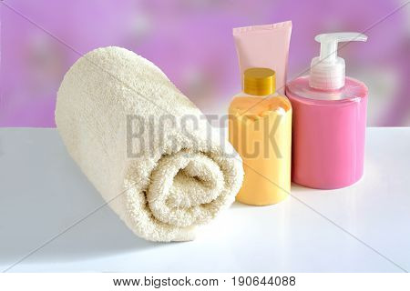 Natural hypoallergenic herbal Cosmetic products for skin care: plastic dispenser with liquid soap bottle of lotion tube of cream and white terry cotton towel on a pink floral blurred background