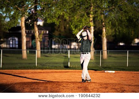 A 16 year old teenage boy in green and grey baseball uniform standing on the pitchers mound going through the motion of throwing the ball