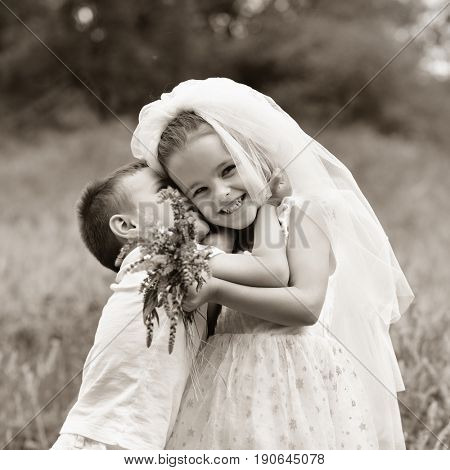 Young bride and groom playing wedding summer outdoor. Children like newlyweds. Little girl in bride whote dress and bridal veil kissing her little boy groom, kids game, sepia toned like old photo