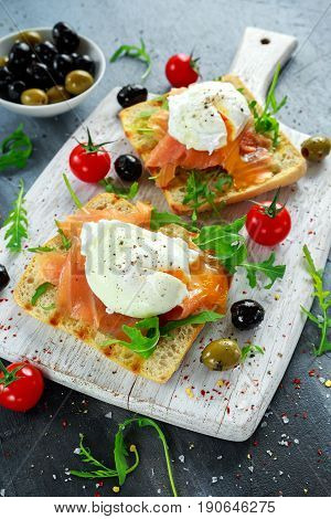 Poached egg on grilled toast with smoked salmon, rucola, olives and vegetables on white board. healthy breakfast.