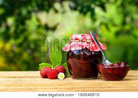 strawberry jam in jar and bowl with spoon, fresh berries on wooden table with green blurred natural background. Preserved fruits. Homemade jam in jar covered with paper. Still life with copy space