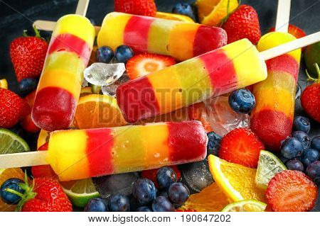 Healthy refreshing fruit popsicle lollies with orange, lime, strawberries, blueberries