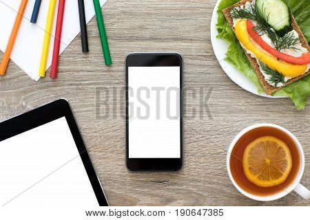 Phone and computer tablet with isolated screen on wooden table in cafe with colorful pencils