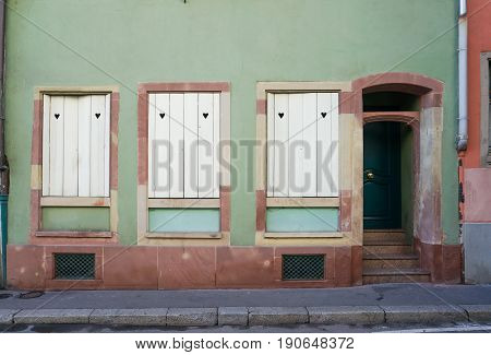 Pastel green and dark brown building with white windows and door beside the street in Colmar France.