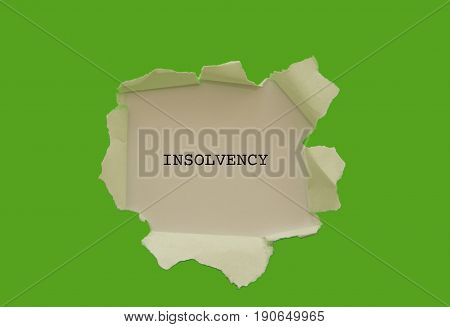 Insolvency word written under torn paper concept .