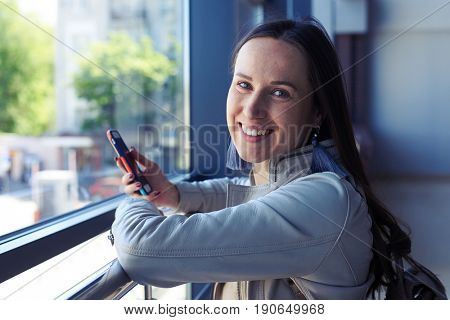 Close-up of charming woman surfing in phone while leaning on handrail