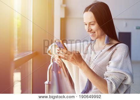 Mid shot of graceful lady surfing in phone while leaning on handrail with copy space