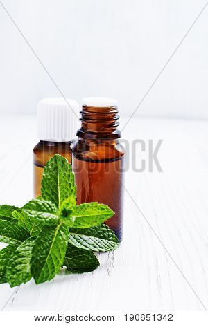 Essential oil of peppermint in dark bottles , fresh green mint on white wooden background selective focus