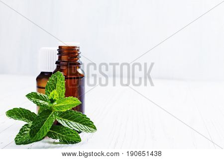 Essential oil of peppermint in dark bottles  on white wooden background selective focus