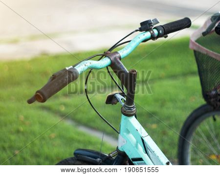 Hands in gloves holding handlebar of a bicycle.