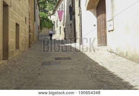 Senior man walking in a medieval street in Trujillo Spain. Old town