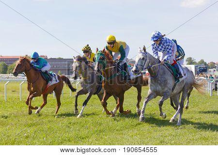 STOCKHOLM SWEDEN - JUNE 06 2017: Four jockeys side by side riding gallop arabian race horses at Nationaldags Galoppen at Gardet. June 6 2017 in Stockholm Sweden