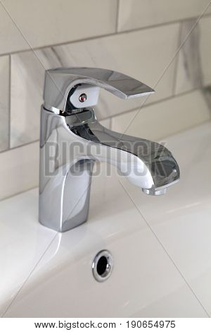 close up view of chrome faucet in modern bathroom, selective focus
