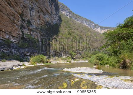 La Venta River flowing in deep Rio la Venta Canyon surrounded by steep cliffs and tropical vegetation on sunny day in Chiapas Mexico