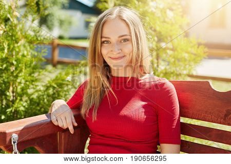 Outdoor shot of adorable young female with brilliant eyes fair hair and freckles dressed in red sweater sitting at bench over green background admiring landscapes. People vacation and leisure concept