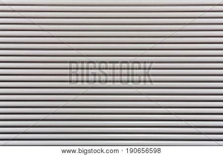 White plastic protective roller blinds. Side lighting of the sun. Horizontal stripes