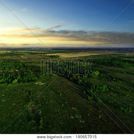 Beautiful view of the fields with trees on it at sunset. Aerial view. From above. Picture taken using the copter.