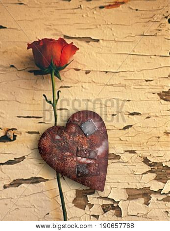 Surrealism. Red rose and rusted heart with metal patches.