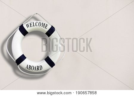 White Color Life Buoyancy With Welcome Aboard On It Hanging On White Concrete Wall.had Space On Righ
