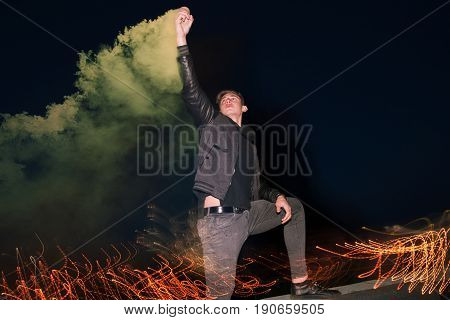 Crazy male fan with smoke bomb at night. Hooligan guy with protest sign in hand on night lights background.