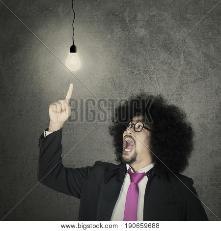Afro businessman wearing formal suit and pointing at bright light bulb. Concept of new ideas innovation invention and creativity
