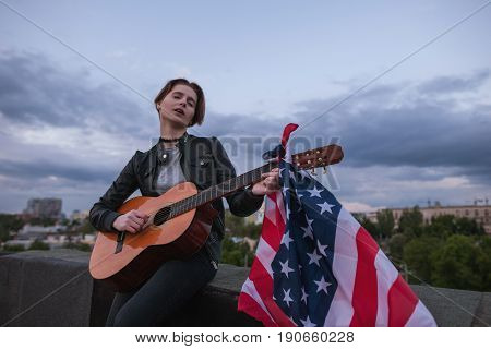 Singer with the US flag playing the guitar on cloudy sky background. Acoustic concert on the roof. A teenager on vacation at a party on Independence Day