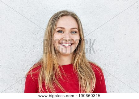 Cheerful blonde woman with freckled face charming eyes and sincere smile having pleased look while standing against white concrete wall. Bright lovely female with joyful expression. Positive emotions