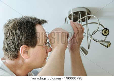 Electrician is installing a LED light bulb in a ceiling lamp.
