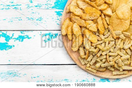Round wooden board with dry salty snacks for beer on the old blue table. Top view.