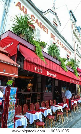 PARIS - JULY 1: View of typical paris cafe on Julne 1, 2017 in Paris. Montmartre area is among most popular destinations in Paris, Au cadet de Gascogne is a typical cafe.