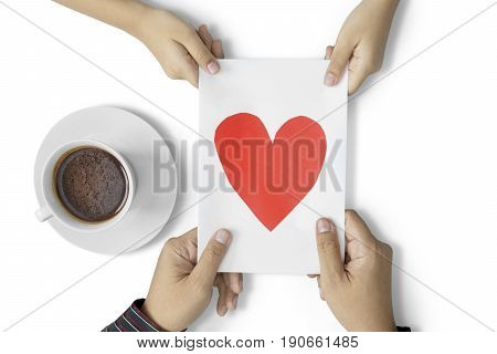 Child giving greeting card to her father with a cup of coffee on the table isolated on white background
