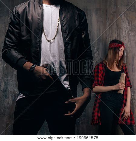 Guy with gun and girl with alcohol. Criminal teenagers on dark background. Gang members lifestyle