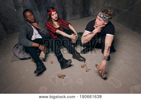 Group of homeless gung members gets drunk. Youth addiction problem. Tired drunk caucasian girl holding alcohol bottle, sad and depressed guys with tattoo sits near . Social problem concept