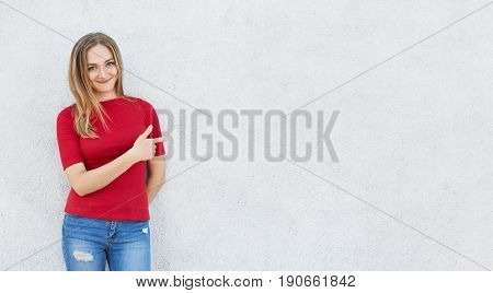 Horizontal portrait of cute woman wearing red sweater and jeans standing near white concrete wall poiting with her index finger at copy space for your adverisment text or logo. Advertising concept