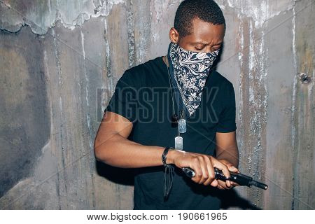 Black gang member checks his weapon. Gangster man with gun in hand on dark gray background. Outlaw, ghetto, murderer, armed attack concept