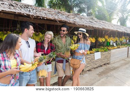 People Group Buying Bananas And Pineapples On Street Traditional Market, Young Man And Woman Travelers Choosing Fresh Fruits