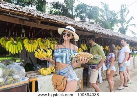 Woman Hold Bananas And Pineapple On Street Traditional Market, Young Man And Woman Travelers Choosing Fresh Fruits