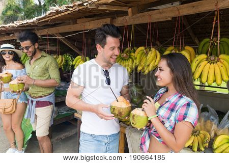 Couple Drink Coconut Cocktail On Street Traditional Fruits Market, Young Man And Woman Travelers