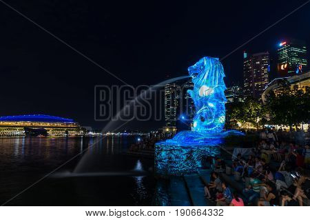 Singapore - March 25 2017: Night scene of Merlion in Marina Bay area and Financial buildings in background