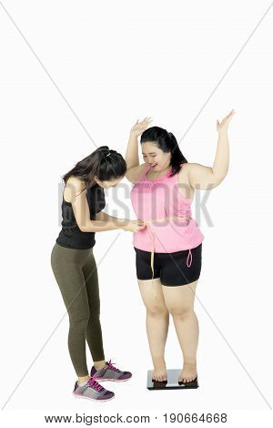 Instructor measuring waist of fat woman with measurement tape while standing on weight scale isolated on white background