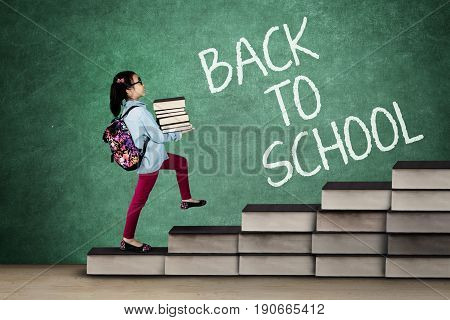 Back to School concept. Little school girl carrying book and rucksack while stepping on the stair made of book