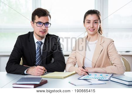 Business people are looking into the camera while working in the office