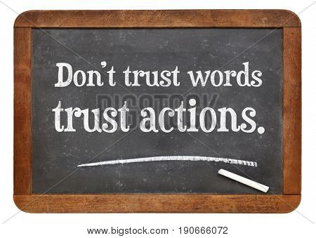 Don't trust words, trust actions - white chalk text on a vintage slate blackboard