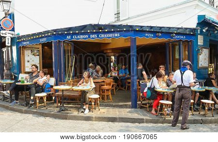 PARIS , France- June 01, 2017: View of typical paris cafe in Paris. Montmartre area is among most popular destinations in Paris, Au clairon de chasseur is a typical cafe.
