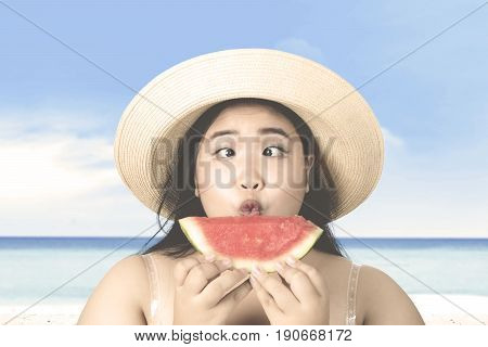 Summer holiday concept. Overweight woman with squint-eyed holding and looking at fresh watermelon while wearing hat on the beach