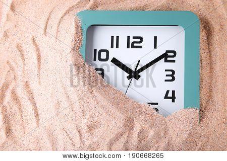 Green clock on the beach sand, close up