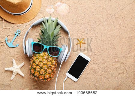 Ripe Pineapple With Sunglasses And Headphones On Beach Sand