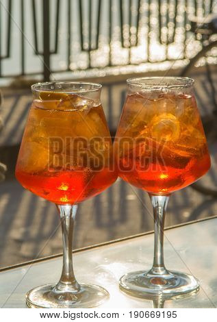 Waiter prepared the orange summer cocktail with prosecco ice cubes and orange liquer in wine glass ready to drink on sunny terrace with sea view