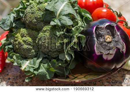 Ripe violet eggplant ball with broccoli and red tomatoes fresh healthy vegetables ready to cook